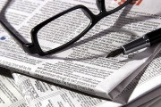 a newspaper, with reading glasses and fountain pen
