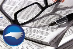 north-carolina map icon and a newspaper, with reading glasses and fountain pen