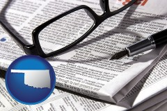 oklahoma map icon and a newspaper, with reading glasses and fountain pen