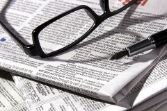 newspaper, with reading glasses and fountain pen