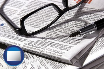 a newspaper, with reading glasses and fountain pen - with Colorado icon