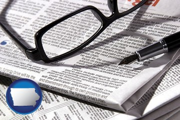 a newspaper, with reading glasses and fountain pen - with Iowa icon