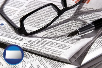 a newspaper, with reading glasses and fountain pen - with Kansas icon