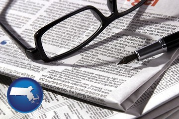 a newspaper, with reading glasses and fountain pen - with Massachusetts icon