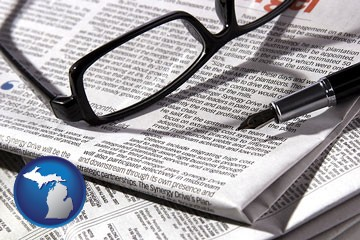 a newspaper, with reading glasses and fountain pen - with Michigan icon