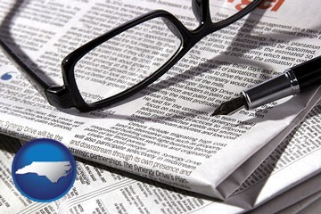 a newspaper, with reading glasses and fountain pen - with North Carolina icon