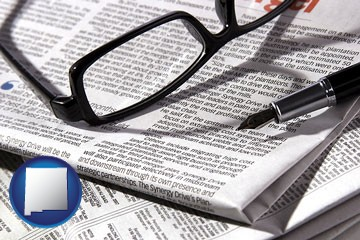 a newspaper, with reading glasses and fountain pen - with New Mexico icon