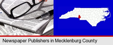 a newspaper, with reading glasses and fountain pen; Mecklenburg County highlighted in red on a map